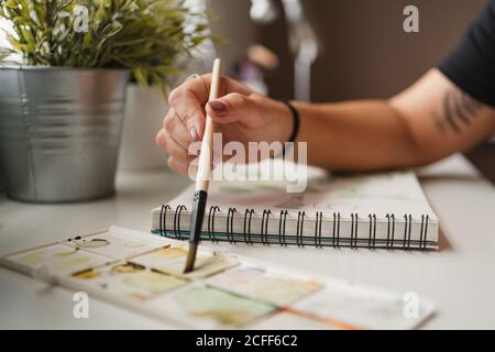 Closeup of unrecognizable woman using palette and watercolors while creating picture and sitting at table at home in Paris