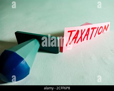 Taxation word displayed on paper slip concept for educational informative awareness.