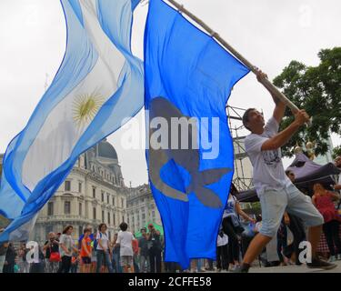 Buenos Aires, Argentina; March 24th: Man waves an Argentine flag in the Plaza de Mayo. - Stock Photo