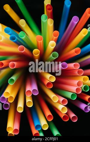 From above multicolored plastic straws for drinking cocktails on black background