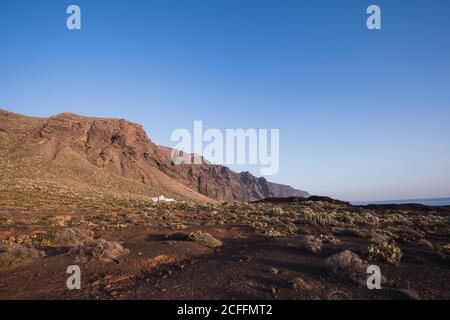 Picturesque view of high rocky cliffs on desert seashore against blue clear sky in Spain
