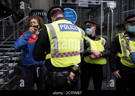 Police talk to a young man who has his hand on a Blue plaque which talks of links to slavery and fossil fuel projects which was pasted up outside the Lloyd's of London building on the Walk of Shame disruptive mach through the City of London by environmental group Extinction Rebellion on 4th September 2020 in London, United Kingdom. The walk visited various locations in the financial district, to protest against companies and institutions with historical links to the slave trade, or who finance or insure projects which are seen as ecologically unsound. The message by the group is that 'apologie