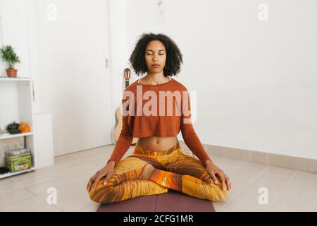 African American attractive young woman performing yoga pose with legs crossed and meditating with closed eyes at home