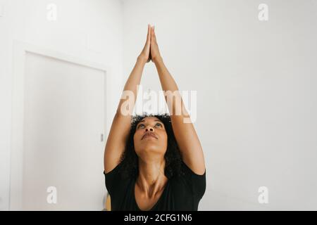 African American attractive young woman performing yoga posture with stretched arms on mat in light room