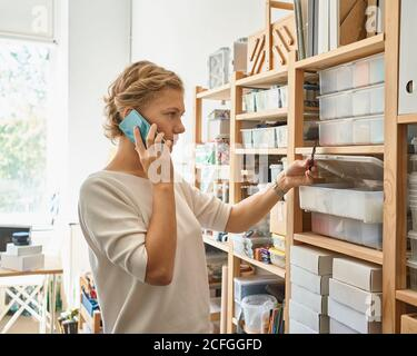 Manufacture of glass products, workpiece. Young female entrepreneur speaking on mobile phone and looking on shelves, happy lady in sunny day in workshop. Women's small business - Stock Photo