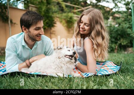 Happy couple of guys playing with their dog in the backyard on the grass. Cheerful old dog