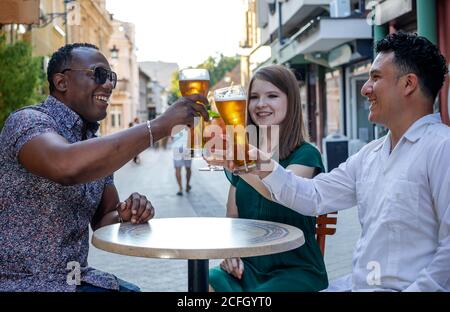 Multiracial group of friends drinking and toasting at street terrace of the cafe. Friendship concept with young multi ethnic people enjoying time toge