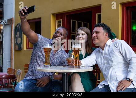 Multiracial group of friends drinking and taking selfie at street terrace of the cafe. Friendship concept with young multi ethnic people enjoying time