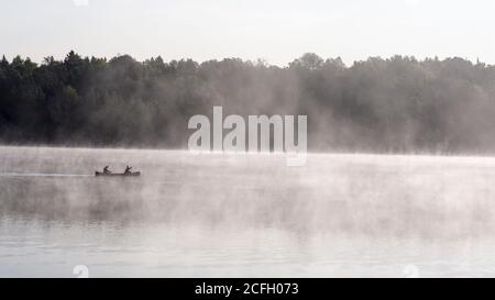 Misty Morning Paddle: Two people paddle a canoe through the early morning mist on a calm lake as the rising sun highlights the rising fog from the warm lake. - Stock Photo