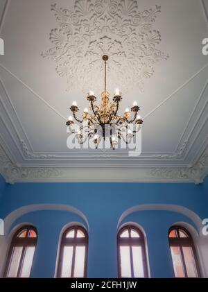 Beautiful golden chandelier suspended down a white ornate ceiling inside a palace room with blue walls and arched windows. Different geometric shapes,