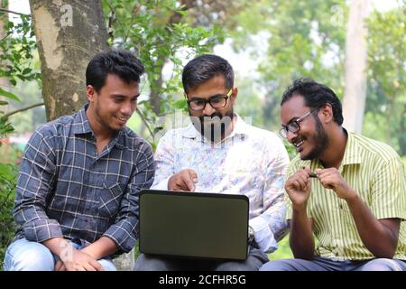Two Asian students discussing an academic topic with their mentor outside on the university campus with smiles on their faces