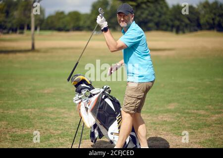 Middle-aged man playing a round of golf on a golf course turning to smile at the camera as he selects a club from his bag for the next shot