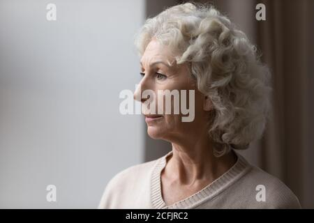 Close up upset thoughtful mature senior woman looking out window