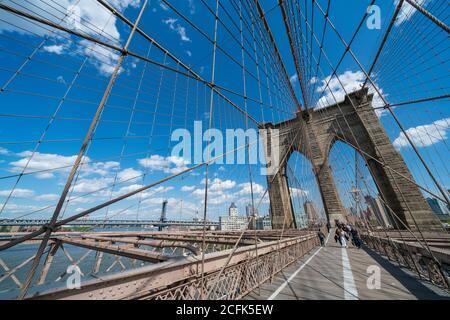 People walk down the Brooklyn Bridge Promenade at New York City.