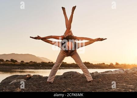 Strong man with slender woman on back balancing with raised crossed legs while practicing acro yoga during sunset in summer
