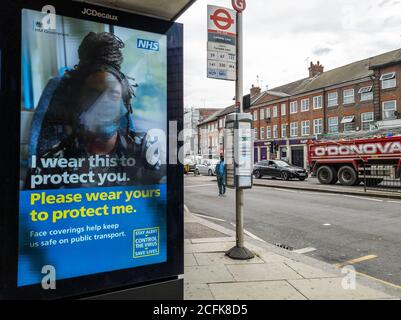 Billboard advertisement by the NHS telling people to wear a face covering as a Covid-19 pandemic safety measure. - Stock Photo