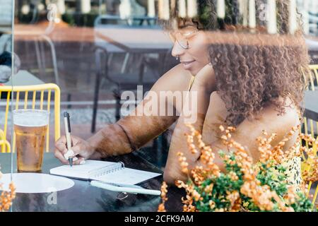 Side view of black self employed woman sitting at table in cafe and working remotely while writing in notepad