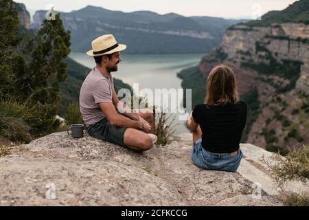 Traveling couple sitting on hill and drinking hot coffee while enjoying majestic view of highland landscape - Stock Photo
