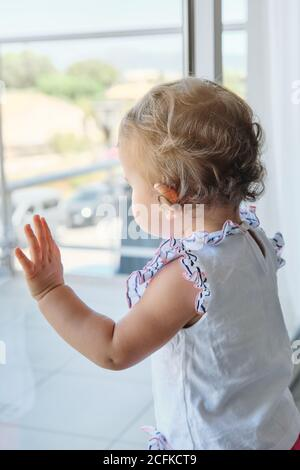 Vertical photo of a little girl standing with her hands on a window looking at the outside of a house - Stock Photo