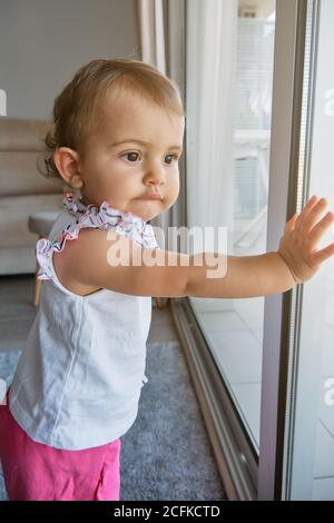 Vertical photo of a little girl standing with her hands on a window looking at the outside with distracted expression in a house - Stock Photo