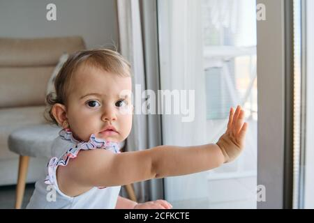 Little girl standing with her hands on a window looking at a side with distracted expression in a house - Stock Photo