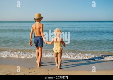 Two children in swimsuits holding hands walking towards the sea water together - Stock Photo