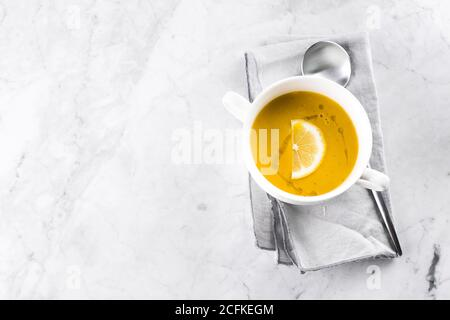 Lentil soup in the white bowl on marble table. Top view. - Stock Photo