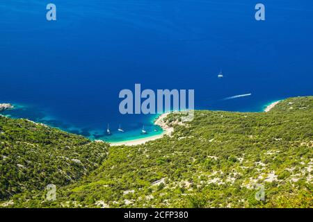 Croatia, island of Cres on Adriatic sea, amazing panoramic view of azure lagoon and beach under Lubenice town on sunny day. - Stock Photo
