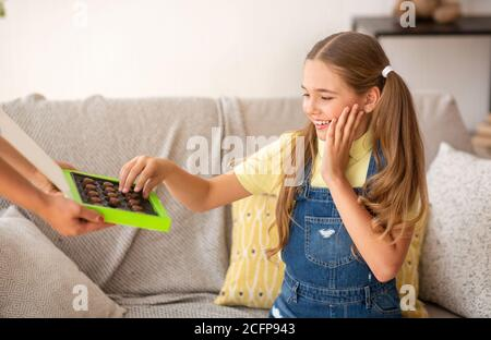 Girl taking chocolate sitting on a couch at home - Stock Photo