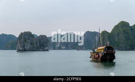 Cat Ba, Vietnam - November 19, 2019 : Junk boat cruising in Lan Ha Bay near Ha Long Bay, mountain karst in background, sea, overcast sky. - Stock Photo
