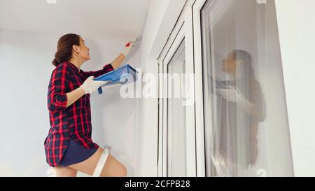 young woman in shorts and red checkered shirt goes up step ladder with tray to paint wall on modern spacious glazed loggia at home repair - Stock Photo