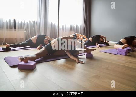 Portrait of happy young women doing stretching exercise in gym - Stock Photo