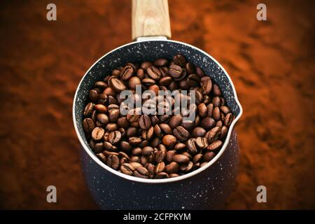 Against the background of ground coffee is a beautiful blue-spotted cezve, for brewing coffee, completely filled with roasted coffee beans. Favourite