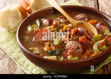 Delicious hot sausage lentil soup with seasonal vegetables close-up in a plate on the table. horizontal - Stock Photo