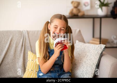 Girl eating chocolate sitting on a couch at home - Stock Photo