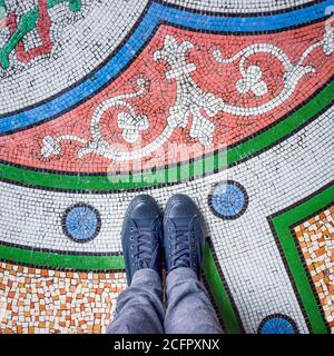 Feet selfie with black shoes on colorful beautiful mosaic tiles floor, top view