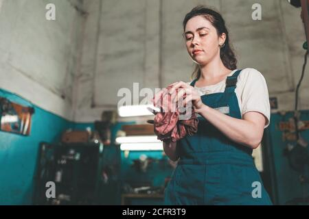 Gender equality. Portrait of a young woman in uniform, working in a workshop, which wipes his hands with a rag. Bottom view. Auto shop in the backgrou
