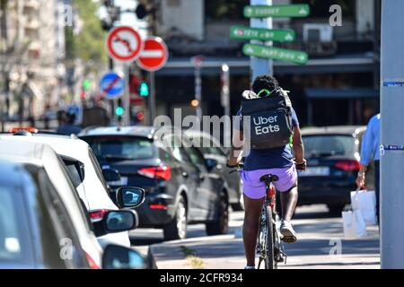 Lyon (central-eastern France). Uber Eats delivery man viewed from behind riding a bike - Stock Photo
