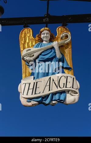 This angelic musician with gilded hair & wings holds a three-stringed rebec, an instrument with Middle Eastern & Persian origins popular in Western Europe from the 1200s to the 1500s, graces the Market Place of the historic wool town of Lavenham in Suffolk, England, UK, as the inn sign of the Angel Hotel.  The Angel, first licensed in 1420, is thought to be the town's oldest inn.  It was chiefly formed from a 15th century timber-framed building, although 14th century interior wall paintings show earlier origins.  Other features include a 16th century plaster ceiling. - Stock Photo