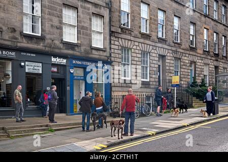 People and their pets queueing and social distancing outside a veterinary practice on DundasStreet, Edinburgh, Scotland, UK. - Stock Photo