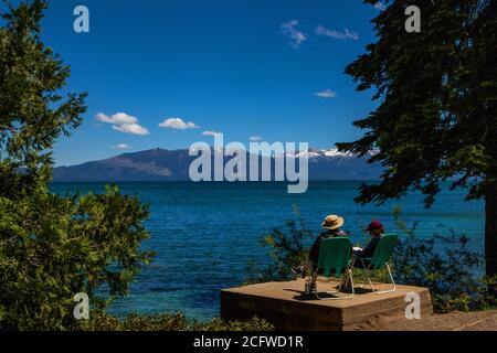 Two people relax in beach chairs on a viewing platform overlooking Lake Tahoe at Sugarpine State Park, California - Stock Photo