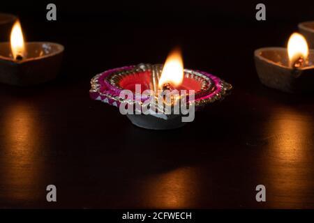 Decorative colourful diya lamps lit during diwali.