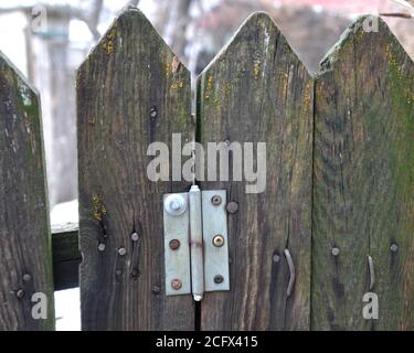 Old wooden fence with hammered bent nails, a loop from the gate. - Stock Photo