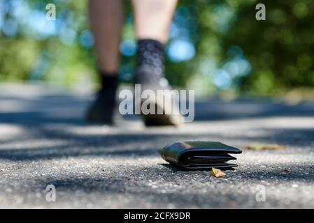 Photo of the sidewalk and legs of a man who lost a black leather wallet while walking