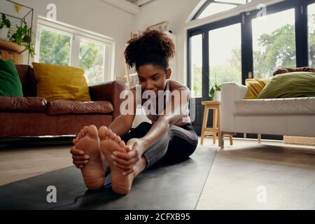 Healthy young woman doing stretching exercise sitting on fitness mat at home