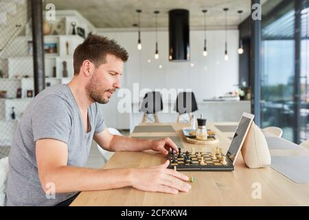 Young man playing chess in video chat online at home in the living room