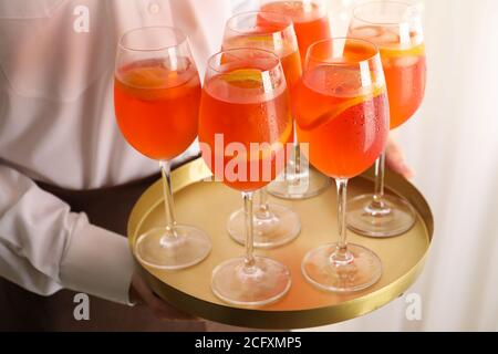 Waiter holding tray with aperol spritz cocktail. Summer drink