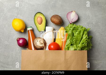 Paper bag with different food on gray background, top view