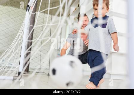 Toddler playing soccer scores a goal together with father in the living room - Stock Photo