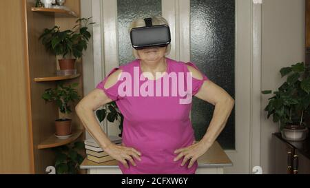 Senior grandmother in virtual headset glasses watching 3D video in VR helmet and training workout home and indoor exercising. Active healthy lifestyle sporty old woman in VR goggles playing games